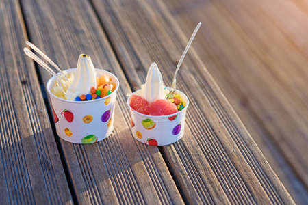 Two cups of ice cream with candies on sunset. Banque d'images - 131784563