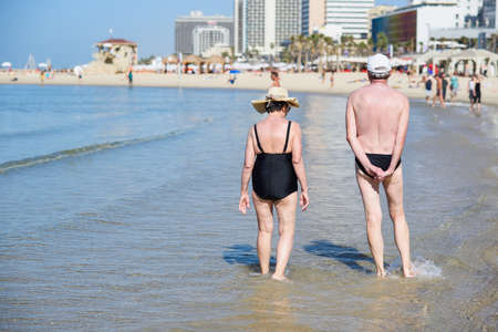 Senior couple walking on beach. Old man and woman in love have a vacation on seaside. View from back. 写真素材