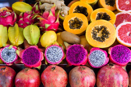 Exotic summer fruits laid out in shopping mall or market. Dragon fruit, pineapple, persimmon, mango, annona cherimola, pomegranate, carambola, grapefruit. Tropical fruits ready for juice.