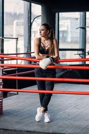 Beautiful sports caucasian girl on boxing ring, have a rest after hard training in modern loft gym.