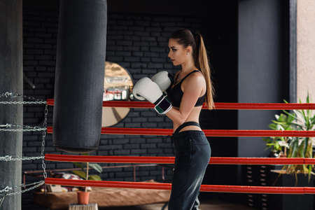 Young beautiful sports girl in sportswear and boxing gloves hits a punching bag in modern black gym. Stock Photo
