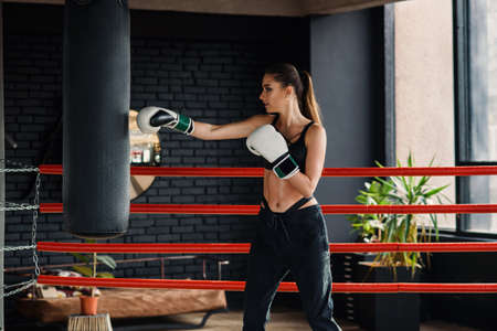 Young beautiful sports girl in sportswear and boxing gloves hits a punching bag in modern black gym. Stok Fotoğraf