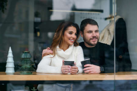 Cute girl with her boyfriend sitting inside a cafe and drinking hot fragrant coffee while outside is cold weather. Love and romance concept. Stockfoto - 132229242