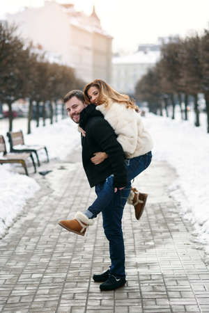 Healthy man holds his pretty girlfriend on the hands on background of winter snowy street. New Year and Christmas concept.