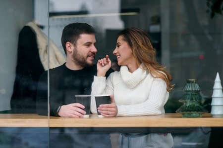 Cute girl with her boyfriend sitting inside a cafe and drinking hot fragrant coffee while outside is cold weather. Love and romance concept. Stockfoto - 132229239