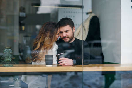 Beautiful caucasian couple drink coffee on a date, and having fun together.