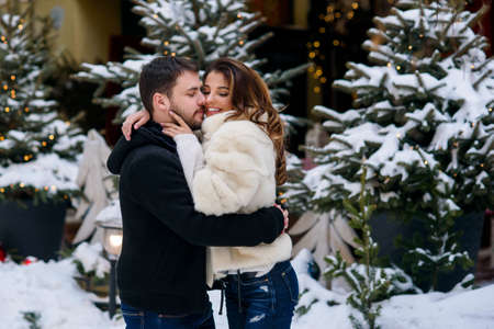 Happy couple in warm clothes hugging each other on the background of christmas tree with lights. Winter holidays, Christmas and New Year concept. Stockfoto - 132229244