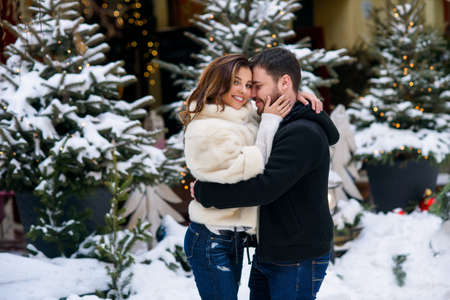 Happy couple in warm clothes hugging each other on the background of christmas tree with lights. Winter holidays, Christmas and New Year concept. Stockfoto - 132229380