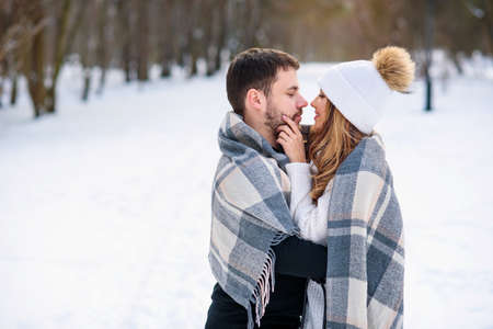 Beautiful girl in white warm hat and her boyfriend hugging each other and covered with checkered plaid while walking in snowy winter park.