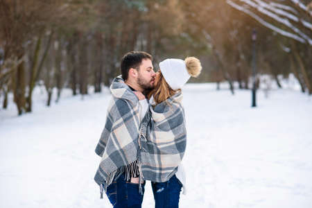 Beautiful couple hugging each other and covered with checkered plaid. Handsome man kisses his pretty girlfriend in winter park.