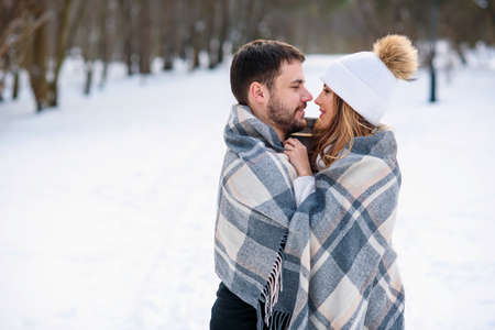 Beautiful couple hugging each other and covered with checkered plaid while walking in snowy winter park.