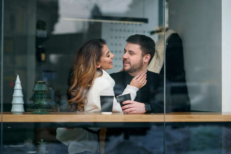 Cute girl with her boyfriend sitting inside a cafe and drinking hot fragrant coffee while outside is cold weather. Love and romance concept. Stockfoto - 132229399