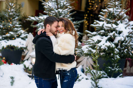 Happy couple in warm clothes hugging each other on the background of christmas tree with lights. Winter holidays, Christmas and New Year concept. Stockfoto