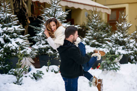 Handsome man holds his beautiful smiling girlfriend on his shoulder on the background of christmas tree with lights. Winter holidays, Christmas and New Year concept. Stockfoto - 132229405