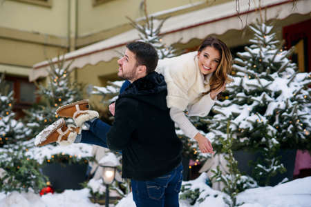 Happy young couple having fun on winter cityscape background of christmas tree with lights. Winter holidays, Christmas and New Year concept. Stockfoto - 132229408