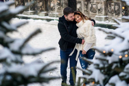 Happy young couple having fun on winter cityscape background of christmas tree with lights. Winter holidays, Christmas and New Year concept.