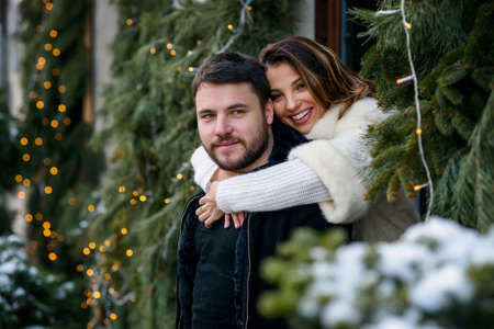 Happy couple in warm clothes hugging each other on the background of christmas tree with lights. Winter holidays, Christmas and New Year concept. Stockfoto - 132229410