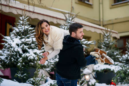 Handsome man holds his beautiful smiling girlfriend on his shoulder on the background of christmas tree with lights. Winter holidays, Christmas and New Year concept. Stockfoto