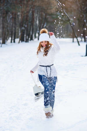 Beautiful young woman weared in white sweater and hat with ice skates on the hands having fun in winter snowy park. Stockfoto - 132229695