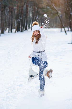 Beautiful young woman weared in white sweater and hat with ice skates on the hands having fun in winter snowy park. Stockfoto - 132229720