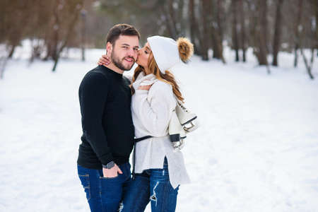 Beautiful couple in love hugging each other while walking in a winter Park.