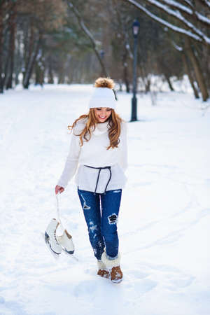 Beautiful young woman weared in white sweater and hat with ice skates on the hands having fun in winter snowy park. Stockfoto