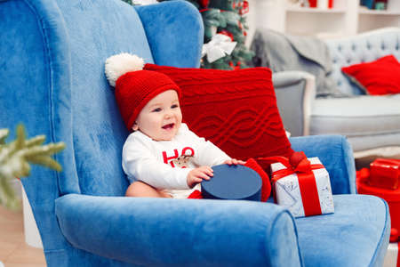 Beautiful little baby boy in christmas clothes sits in blue big chair and holding gift box in his hands. Stockfoto - 132229731