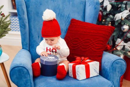 Beautiful little baby boy in christmas clothes sits in blue big chair and holding gift box in his hands.