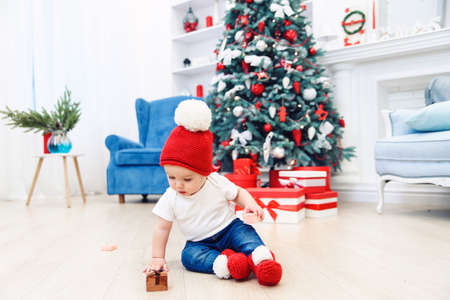 Toddler boy weared in festive clothes playing with christmas gift box. Concept of Christmas and New Year holidays. Stockfoto - 132229735