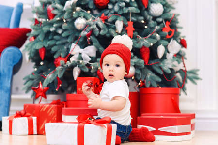 Toddler boy weared in festive clothes playing with christmas gift box. Concept of Christmas and New Year holidays.
