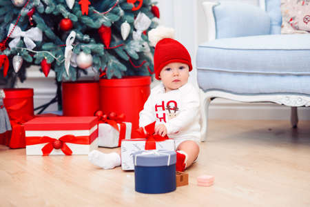 baby unpack gift boxes with christmas decoration, dressed as Santa, boke lights on dark background, winter holiday concept Stock Photo