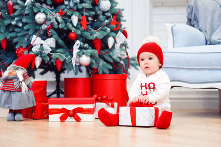 Charming toddler boy holds christmas gift box. Concept of Christmas holidays.