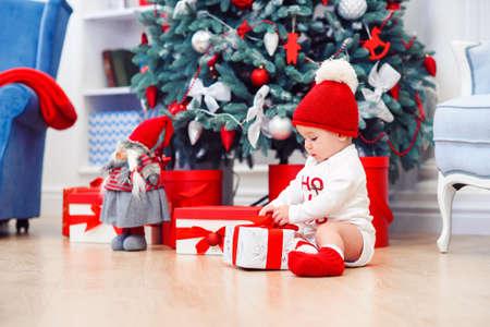 Charming toddler boy holds christmas gift box. Concept of Christmas holidays. Reklamní fotografie - 132229742