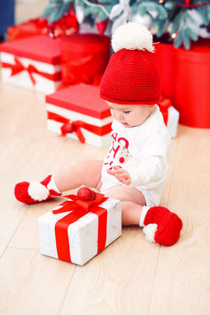 Funny infant baby girl unpacks christmas gift box. Merry Christmas and Happy New Year.