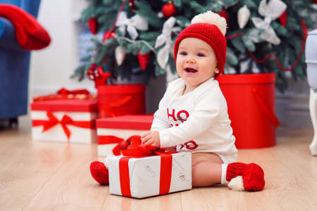 Charming toddler boy holds white christmas gift box with red ribbon. Funny cute baby weared in festive clothes in Christmas decorated room. Concept of Christmas and New Year holidays.