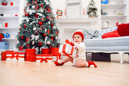 Charming toddler boy holds christmas gift box. Concept of Christmas holidays. Reklamní fotografie - 132229747