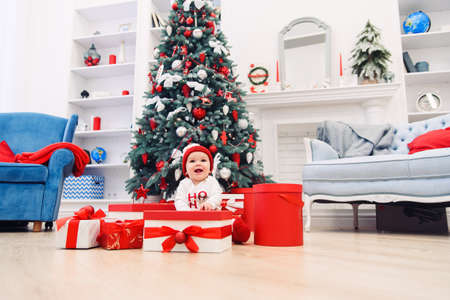 Charming toddler girl holds white christmas gift box with red ribbon. Funny cute baby weared in festive clothes in Christmas decorated room. Concept of Christmas and New Year holidays. Stockfoto