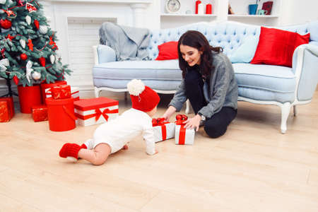Adorable smiling infant crawling on the parquet to the christmas gifts near his mom which sits on the floor.