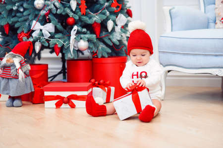 Funny infant baby girl unpacks christmas gift box. Merry Christmas and Happy New Year. Stockfoto - 132229993