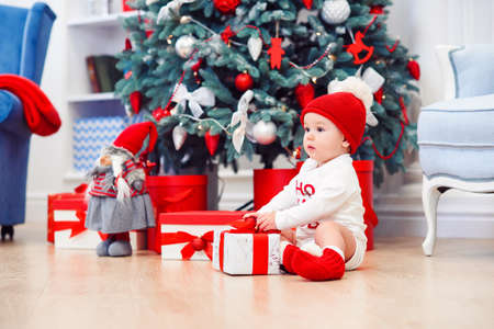 baby unpack gift boxes with christmas decoration, dressed as Santa, boke lights on dark background, winter holiday concept Stockfoto - 132229997