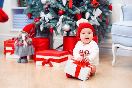baby unpack gift boxes with christmas decoration, dressed as Santa, boke lights on dark background, winter holiday concept Stockfoto - 132230001