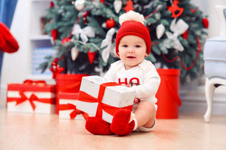 baby unpack gift boxes with christmas decoration, dressed as Santa, boke lights on dark background, winter holiday concept Stockfoto - 132229998