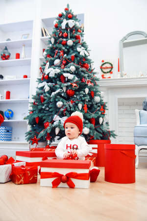 baby unpack gift boxes with christmas decoration, dressed as Santa, boke lights on dark background, winter holiday concept Banque d'images