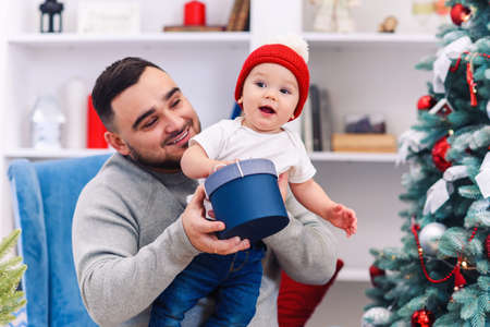 Young father sits in comfortable chair holding amusing toddler and gives gift box to him in the wonderfully decorated room to celebrate christmas. Stockfoto - 132230002
