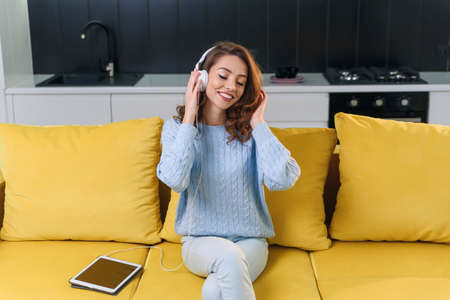 Adorable modern woman with wavy brown hair dressed in stylish casual clothes resting on the comfortable sofa in the kitchen and listens to music in headphones. Cozy home concept.