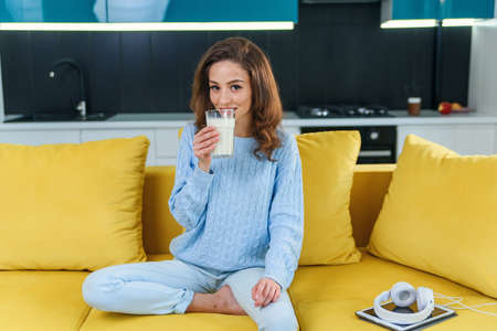 Attractive woman holds a glass of fresh milk and drinks it in the stylish cozy kitchen at the morning. Healthy drinks. Stockfoto