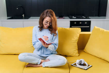 Beautiful happy girl in eyeglasses writes her personal notes into her diary while sitting in the modern stylish kitchen. Stok Fotoğraf - 132152984