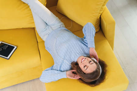 Satisfied cheerful girl lying on the comfortable yellow couch and listens to the music on her white earphones. Top view.