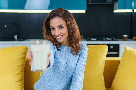 Attractive smiling woman gives to the camera a glass of fresh milk in the stylish cozy kitchen at the morning. Pretty healthy girl holds a glass of fresh milk on foreground. Selective focus. Stockfoto