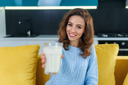 Smiling woman gives to the camera a glass of fresh milk in the stylish cozy kitchen at the morning. Pretty healthy girl holds a glass of fresh milk on foreground. Stockfoto - 132629489